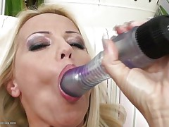 Blonde milf wearing only a pair of sexy black stockings is playing solo with her big dildo, she sucks it and the fills her shaved vagina with it, fucking herself as hard as she can but that is not enough. Luckily her brunette girlfriend is willing to help and gives her a hand, rubbing her cunt and then fingering it, wanna see what else she's willing to do?